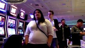 Eine Seite von den Leuten, die Spielautomaten mit den Leuten vorbei überschreiten spielen stock footage