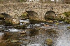 Eine Seitenansicht der Steinsaumpferdbr?cke ?ber dem Ostpfeil-Fluss in Nationalpark Dartmoor, England stockbild