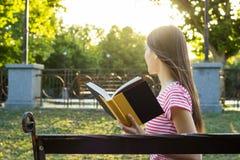 Eine Seitenansicht des erstaunlichen jungen Mädchens, das ein Buch im Park am sonnigen Tag des Sommers liest Stockfoto