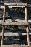 Eine selbst gemachte Leiter lehnt sich an einer Blockhauswand Stockfotos