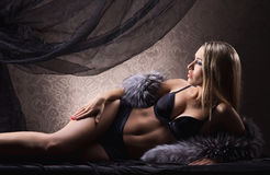 Eine sexy blonde Frau, die in erotische Wäsche und in Pelz legt Stockfotos