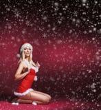 Eine sexy blonde Frau in erotischer Sankt-Wäsche auf dem Schnee Stockfoto