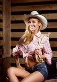 Eine sexy Cowgirlfrau, die in einer Scheune aufwirft Stockbild