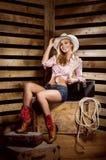 Eine sexy Cowgirlfrau, die in einer Scheune aufwirft Lizenzfreie Stockfotos