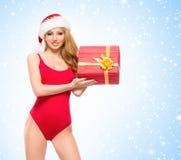 Eine sexy Frau in der roten Weihnachtswäsche, die ein Geschenk hält Stockfoto