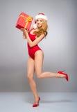 Eine sexy Frau in der roten Weihnachtswäsche, die ein Geschenk hält Stockbilder
