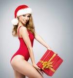 Eine sexy Frau in der roten Weihnachtswäsche, die ein Geschenk hält Lizenzfreie Stockfotos