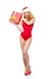 Eine sexy Frau in der roten Weihnachtswäsche, die ein Geschenk hält Stockfotografie