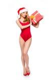 Eine sexy Frau in der roten Weihnachtswäsche, die ein Geschenk hält Stockbild