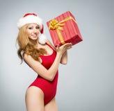Eine sexy Frau in der roten Weihnachtswäsche, die ein Geschenk hält Stockfotos