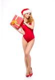 Eine sexy Frau in der roten Weihnachtswäsche, die ein Geschenk hält Lizenzfreie Stockfotografie