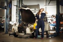 Eine sexy Frau, die ein Auto in einer Garage wäscht Stockfotos