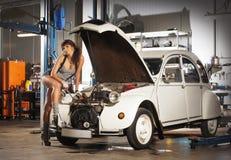 Eine sexy Frau, die ein Retro- Auto in einer Garage repariert Stockbild