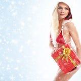 Eine sexy Frau in Sankt kleidet das Halten eines Geschenkes Stockfotografie