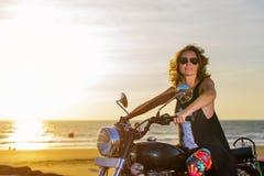 Eine sexy junge Frau in der Sonnenbrille sitzt auf einem schwarzen Chrommotorrad Hippie-M?dchen auf einem Motorrad gegen den Sonn stockfotos