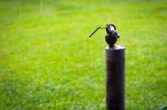 eine sich verjüngende Wasserleitung mitten in einem grünen Feld Stockfoto