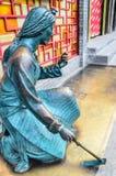 Eine Skulptur der langhaarigen Frau, die eine Hacke verwendet Lizenzfreie Stockbilder