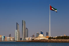 Eine Skylineansicht Abu Dhabis einschließlich die UAE-Staatsflagge Lizenzfreie Stockfotos