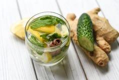 Eine Sommerkälte, die gesundes appetitanregendes Getränk mit Wasser, Zitrone, Ingwer, tadellosen Blättern und Gurke erneuert Stockbilder