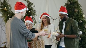 Eine Spaßfirma von jungen Leuten in Santa Claus-Hüten, die Geschenke bei vor Weihnachtsbaum zu Hause stehen austauschen stock video