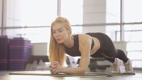Eine Sportlerin führt eine Planke in der Turnhalle durch eingabe