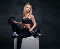 Eine sportliche blonde Frau kleidete in einer grauen Sportkleidung hält Barbell an Stockfotografie