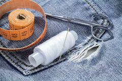 Eine Spule des weißen Threads mit einem Schneider ` s Maßband und der Scheren auf einem Hintergrund des Denims Lizenzfreies Stockfoto