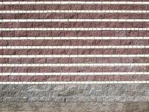 Eine Stützmauer von strukturierten Ineinander greifenblöcken Lizenzfreie Stockbilder