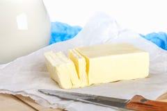 Eine Stange von Butter auf einem hölzernen Brett mit einem Messer, auf einer weißen Tabelle Bestandteile für das Kochen Stockfotografie