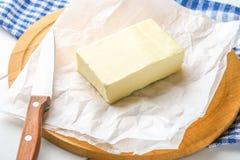 Eine Stange von Butter auf einem hölzernen Brett mit einem Messer, auf einer weißen Tabelle Bestandteile für das Kochen Lizenzfreies Stockfoto