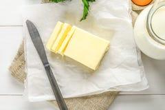 Eine Stange von Butter wird in Stücke auf einem hölzernen Brett mit einem Messer geschnitten, umgeben durch Milch, Eier und Peter Stockbilder