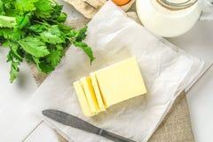 Eine Stange von Butter wird in Stücke auf einem hölzernen Brett mit einem Messer geschnitten, umgeben durch Milch, Eier und Peter Stockbild