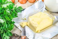 Eine Stange von Butter wird in Stücke auf einem hölzernen Brett mit einem Messer geschnitten, umgeben durch Milch, Eier und Peter Lizenzfreies Stockbild