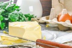 Eine Stange von Butter wird in Stücke auf einem hölzernen Brett mit einem Messer geschnitten, umgeben durch Milch, Eier und Peter Lizenzfreie Stockbilder