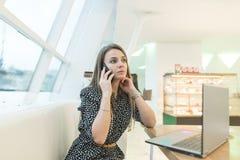 Eine starke Geschäftsfrau löst eine Frage telefonisch beim Sitzen in einem stilvollen hellen Café am Computer Stockbild