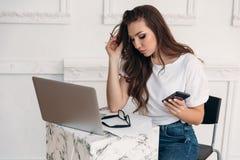Eine starke junge Frau ist mit Arbeit beschäftigt und studiert Dokumente und sitzt an den Laptops und hält ihren Smartphone, wüns lizenzfreies stockbild