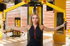 Eine starke und athletische Frau, welche die Übung des Verteilens der Hände auf dem Simulator tut Nahaufnahme Stockfoto
