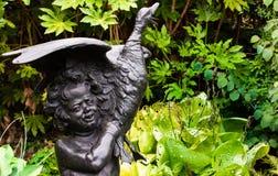 Eine Statue des Kindes mit Ente mit Anlagen im Hintergrund lizenzfreies stockbild