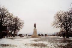 Eine Statue an einem schneebedeckten Park während des Winters lizenzfreies stockfoto