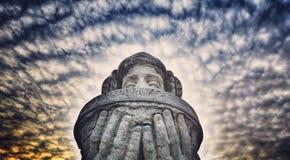 Eine Statue eines Frau ` s Gesichtes mit geschlossenen Augen und dunklen Wolken in Baku, Aserbaidschan Lizenzfreie Stockfotografie