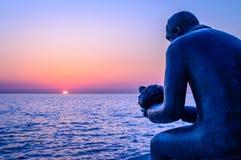 Eine Statue eines Mannes, der ein Seeoberteil durch das Meer bei Sonnenuntergang hält Lizenzfreie Stockfotografie