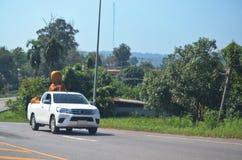 Eine Statue von Buddha sitzt eingewickelt für Schutz auf der Rückseite einer Aufnahme, während sie hinunter die Landstraße reist, stockbild