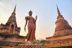 Eine Statue von gehendem Buddha zwischen Stupas in Wat Sa Si Temple an der Dämmerung in historischem Park Sukhothai Stockfoto