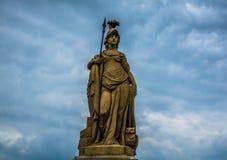 Eine Statue vor dunklen geschwollenen Wolken Stockbild