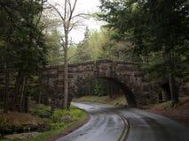 Eine Steinbrücke und eine Fahrbahn an einem feuchten Tag im Acadia-Nationalpark Stockfotos