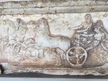 Eine Steinskulptur von Pferden u. von Kampfwagen stockbilder