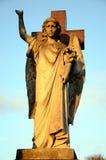 Eine Steinstatue eines geflügelten Engels gegen ein Kreuz bei Sonnenuntergang Lizenzfreies Stockbild