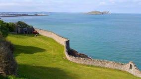 Eine Steinwand auf der Seeküste mit einer Insel im Hintergrund Lizenzfreies Stockfoto