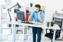 Eine Stellung des jungen Mannes im Büro am Computertisch und Unterhaltung am Telefon stockfoto