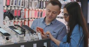 Eine Stellung des verheirateten Paars nahe Schaukasten mit Smartphones im modernen Elektronikladen und einen neuen Smartphone wäh stock video